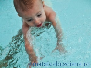 Swimming baby boy reaches for blue ball